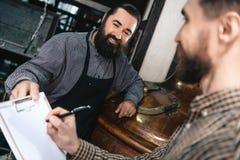 Довольный бородатый винодел в рисберме дает документы для подписывая человека в рубашке в винзаводе стоковое фото rf