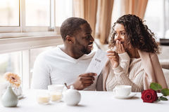 Довольная Афро-американская женщина получая билет от ее парня стоковые изображения rf