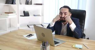 Довольное sittingin бизнесмена его офис работая на его компьютере Стоковые Изображения RF