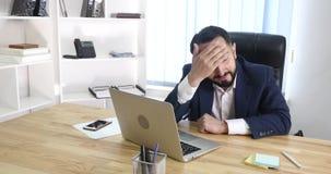 Довольное sittingin бизнесмена его офис работая на его компьютере Стоковые Фотографии RF