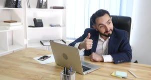 Довольное sittingin бизнесмена его офис работая на его компьютере Стоковое Изображение RF