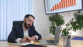 Довольное sittingin бизнесмена его офис работая на его компьютере Стоковое фото RF