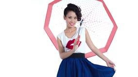 Довольно азиатская девушка с зонтиком при картина точек польки представляя в студии съемка способа акции видеоматериалы