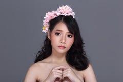 Довольно азиатская молодая женщина с тиарой цветка, присутствующей пустой ладонью Стоковые Фотографии RF