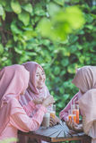 Довольно азиатская мусульманская женщина имея потеху в кафе вместе с frien Стоковое фото RF