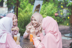 Довольно азиатская мусульманская женщина имея потеху в кафе вместе с frien Стоковая Фотография RF