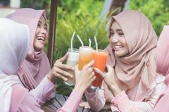 Довольно азиатская мусульманская женщина имея потеху в кафе вместе с frien Стоковые Изображения