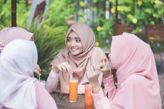 Довольно азиатская мусульманская женщина имея потеху в кафе вместе с frien Стоковая Фотография