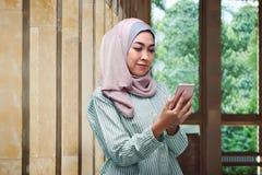 Довольно азиатская мусульманская женщина при вуаль держа мобильный телефон Стоковые Фотографии RF