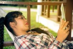 Довольно азиатская таблетка чтения женщины на гамаке Стоковые Изображения RF