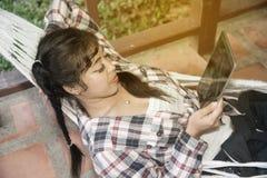 Довольно азиатская таблетка чтения женщины на гамаке Стоковые Фото