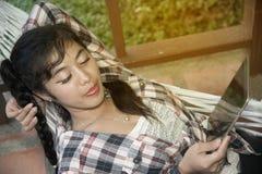 Довольно азиатская таблетка чтения женщины на гамаке Стоковые Изображения