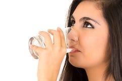 Довольно латинская питьевая вода девушки от стекла Стоковое Фото