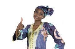 Довольно африканская женщина в традиционных одеждах thumb вверх Стоковое фото RF