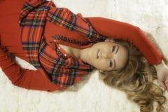 Довольно белокурая девушка в робе & класть рождества красной вниз Стоковая Фотография RF