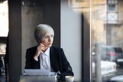 Довольно белокурая девушка сидя в кафе Стоковая Фотография RF