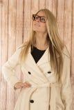 Довольно белокурая женщина в белом пальто и стеклах смотря вверх Стоковые Изображения RF