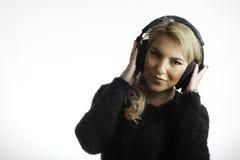 Довольно белокурая нося предпосылка наушников студии слушая изолированная музыкой Стоковое Фото