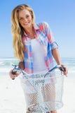Довольно белокурый на езде велосипеда на пляже усмехаясь на камере Стоковая Фотография