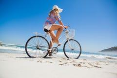 Довольно белокурый на езде велосипеда на пляже Стоковые Фото