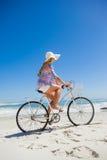 Довольно белокурый на езде велосипеда на пляже Стоковые Изображения RF