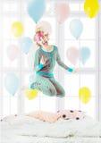 Довольно белокурый околпачивающ вокруг наслаждение скача на кровать стоковые фотографии rf