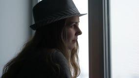 Довольно вскользь женщина стоя на окне, нося шляпе видеоматериал