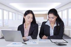 Довольно женские работники обсуждая в офисе Стоковое Изображение RF