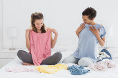Довольно женские друзья выбирая одежды в кровати Стоковые Изображения