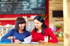 Довольно женские друзья изучая в кафе Стоковые Изображения