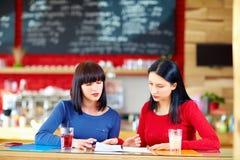 Довольно женские друзья изучая в кафе Стоковое фото RF