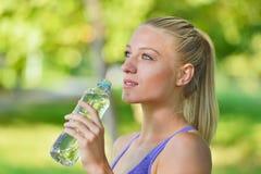 Довольно женский отдыхать и питьевая вода бегуна от бутылки после разработки Стоковые Изображения