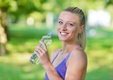 Довольно женский отдыхать и питьевая вода бегуна от бутылки после разработки Стоковая Фотография