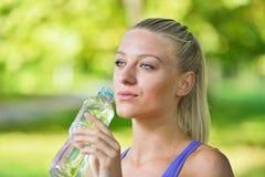 Довольно женский отдыхать и питьевая вода бегуна от бутылки после разработки Стоковое Фото