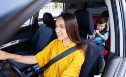 Довольно женский управляя автомобиль при сын сидя в месте младенца Стоковые Изображения RF