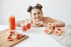 Довольно жизнерадостная девушка с плюшками усмехаясь смотрящ камеру сидя на таблице с кусками диеты вытрезвителя грейпфрута здоро Стоковые Фотографии RF