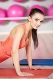 Довольно здоровый делать женщины нажимает вверх на циновке Стоковые Изображения RF