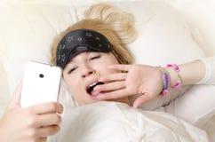 Довольно кавказская белокурая девушка просыпая вверх Стоковая Фотография