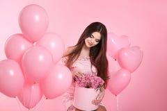 Довольно милая девушка брюнет с воздушными шарами и букет розы пропускают стоковое фото