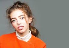 Довольно модная девушка в оранжевой куртке Стоковые Изображения