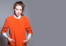 Довольно модная девушка в оранжевой куртке Стоковые Фотографии RF