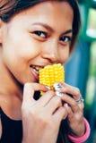 Довольно молодая азиатская женщина есть sweetcorn Стоковая Фотография