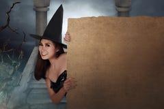 Довольно молодая азиатская женщина одетая как ведьма держа пергамент bo Стоковая Фотография RF