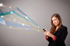 Довольно молодая дама держа телефон с красочным конспектом выравнивает a Стоковые Изображения RF