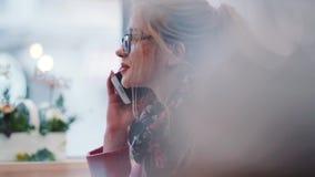 Довольно молодая белокурая девушка в стеклах сидя в уютном café, имеющ телефонный звонок, усмехаться, кивая согласования видеоматериал