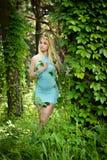 Довольно молодая белокурая девушка с закрытыми глазами и длинные волосы в бирюзе одевают положение в зеленом лесе где деревья enl Стоковое Фото