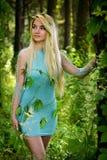 Довольно молодая белокурая девушка с длинными волосами в платье бирюзы стоя в зеленом лесе Стоковые Изображения