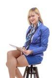 Довольно молодая белокурая женщина при таблетка, сидя на табуретке Стоковые Фото