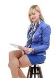 Довольно молодая белокурая женщина при таблетка, сидя на табуретке Стоковая Фотография
