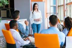 Довольно молодая бизнес-леди давая представление в конференции или встречая установку Стоковая Фотография RF